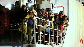 Gerette Migranten warten auf einem Schiff der Küstenwache (Archiv)