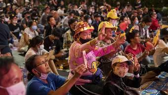 Zahlreiche, regierungskritische Demonstranten mit Mund-Nasen-Schutz zeigen bei einer Kundgebung den drei-Finger-Gruß als Zeichen des Widerstands. Foto: Gemunu Amarasinghe/AP/dpa