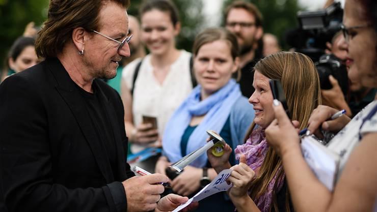 U2-Sänger Bono spricht mit Fans, nachdem er vergangene Woche mit der deutschen Kanzlerin Angela Merkel über Entwicklungshilfe in Afrika gesprochen hat. Bei einem Konzert in Berlin hat am Samstag seine Stimme versagt und die Veranstaltung musste abgebrochen werden.