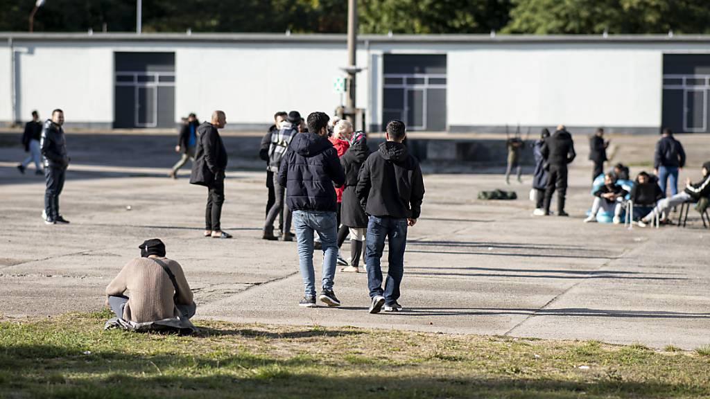 Asylsuchende laufen in der Erstaufnahmeeinrichtung Eisenhüttenstadt über einen Platz. Foto: Fabian Sommer/dpa