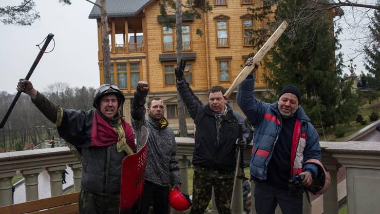 Demonstranten posieren vor der Residenz Janukowitschs.