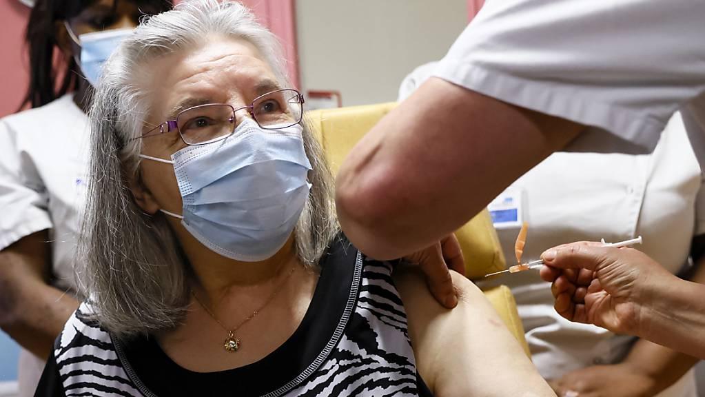 Die 78-jährige Mauricette wird im René-Muret Krankenhaus als erste Frau in Frankreich gegen Corona geimpft. Das stark von der Covid-19-Pandemie betroffene Frankreich hat seine Impfkampagne gegen das Coronavirus begonnen. Foto: Thomas Samson/AFP POOL/AP/dpa