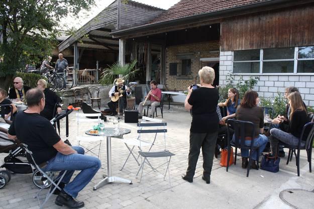 Die Gäste lauschen der Musik vor der Scheune des Biohofs