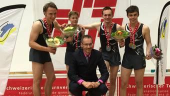 Die Trampolinturner Fabio Hug, Luc Waldner, Cédric Jeannerat und Adrian Simon (v.l.) posieren mit Trainer und Kampfrichter Andy Vogt.