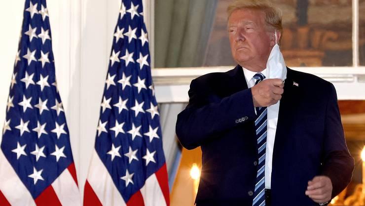 Nichts wie weg damit: Wieder zurück im Weissen Haus, entledigt sich US-Präsident Donald Trump seiner Gesichtsmaske.