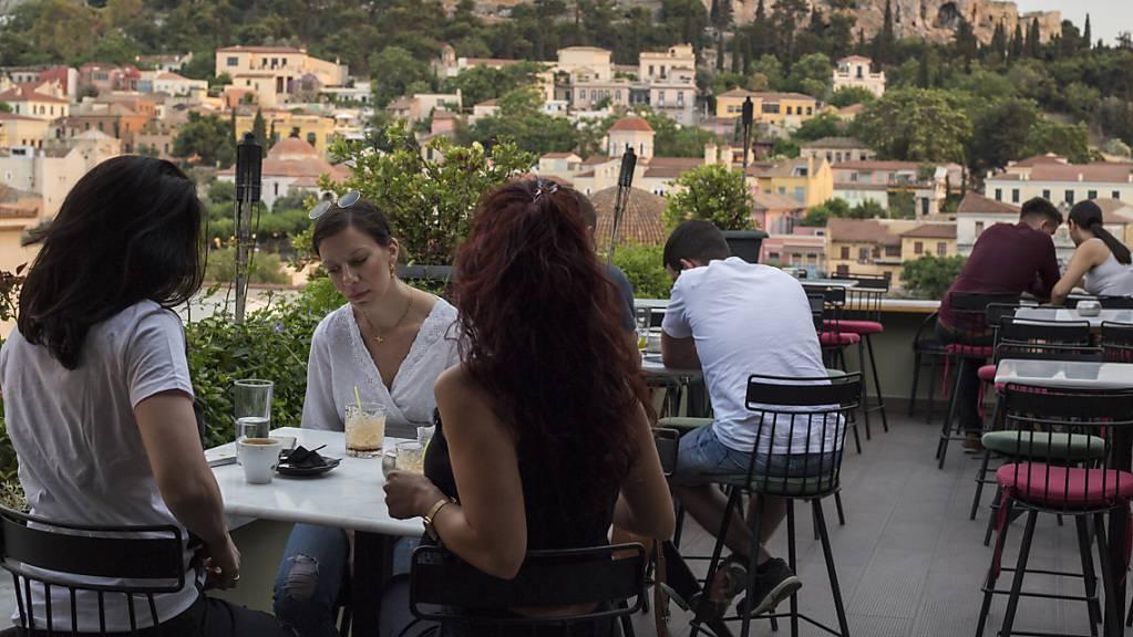 ARCHIV - Ab Montag wieder möglich: Gäste sitzen in einem Cafe in Athen mit der Akropolis im Hintergrund. (Archivbild) Foto: Socrates Baltagiannis/dpa