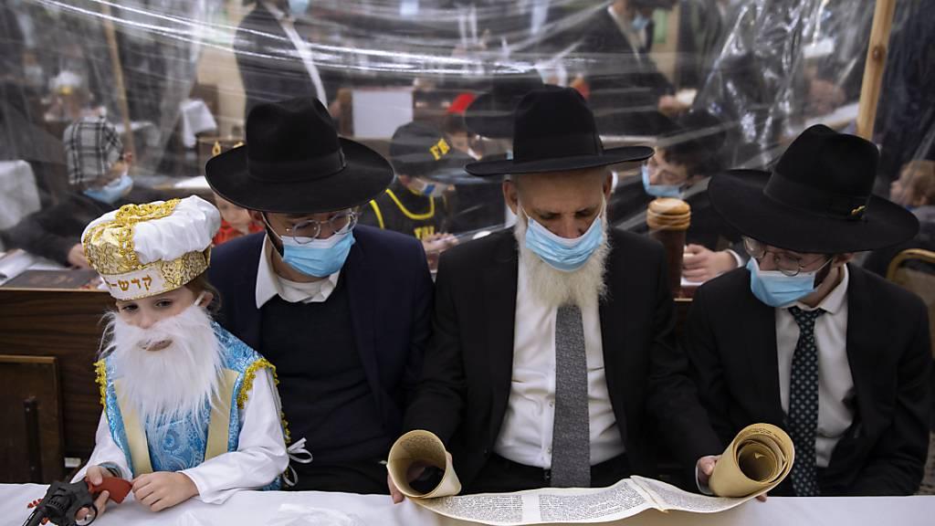 Ultra-orthodoxe Juden feiern das Purimfest mit Sicherheitsvorkehrungen zur Eindämmung der Corona-Pandemie. Andererorts hatte es jedoch zahlreiche Verstöße gegeben. Foto: Oded Balilty/AP/dpa
