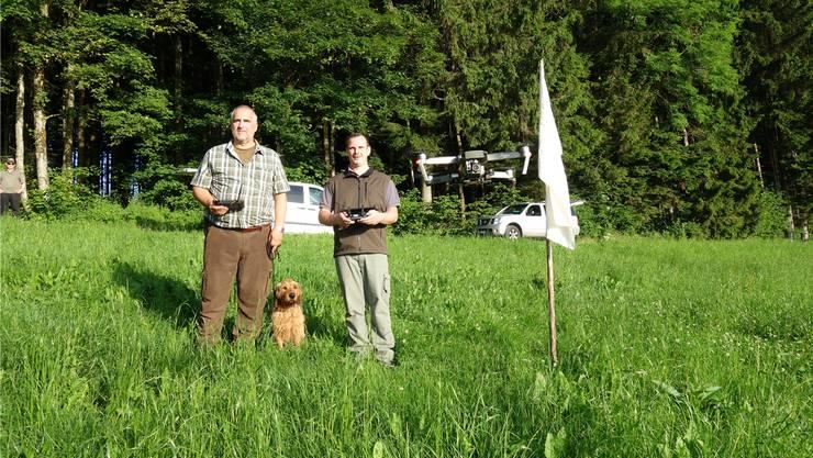 Der Multikopter, hier bedient von Daniel Wyss (rechts), verfügt über eine Wärmebildkamera, die Rehkitze in der Wiese auf dem Bildschirm in der Hand von Adrian Baumberger anzeigt.
