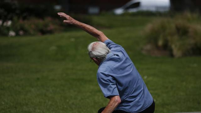 Ein Rentner macht Dehnübungen in einem Park (Symbolbild)