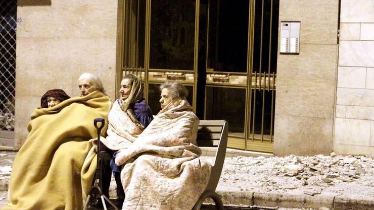 Ältere Frauen beobachten die Bergungsarbeiten.