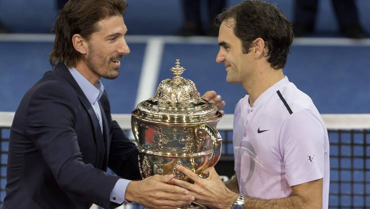Fabiian Cancellara, left, and Roger Federer, right, during the award ceremony after the final between Switzerland's Roger Federer and Argentina's Juan Martin del Potro at the Swiss Indoors tennis tournament at the St. Jakobshalle in Basel, Switzerland, on Sunday, October 29, 2017.