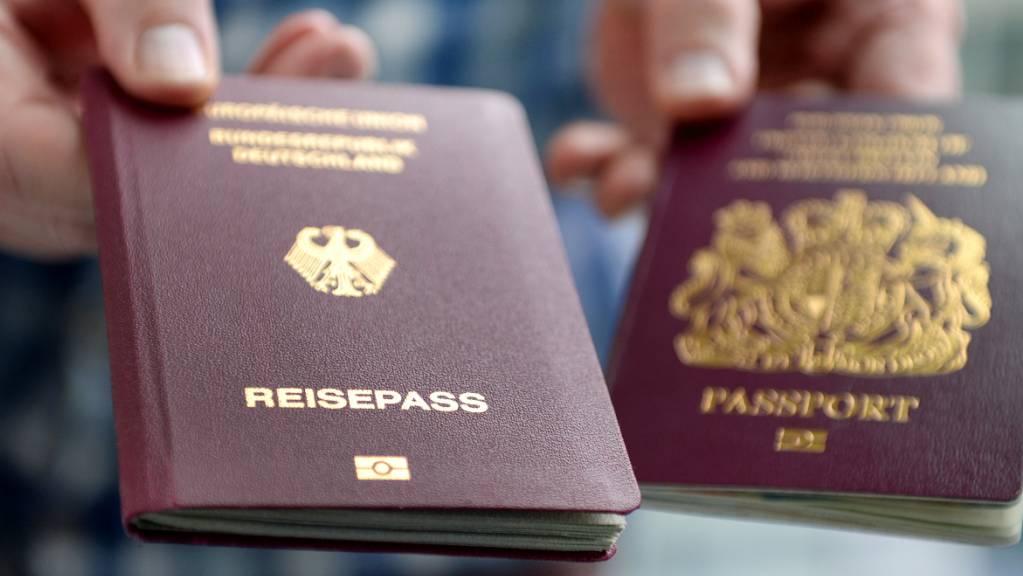 ARCHIV - Ein britischer und ein deutscher Reisepass werden in die Kamera gehalten. Bis auf wenige Ausnahmen reicht ab dem 01.10.2021 an ein Personalausweis nicht mehr aus, um in Großbritannien zu kommen. Künftig brauchen Reisende aus der EU für die Einreise nach Großbritannien einen Reisepass. Foto: Britta Pedersen/zb/dpa