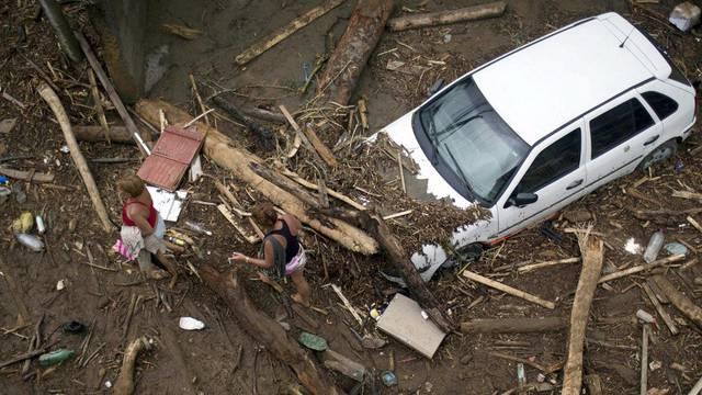 Zwei Anwohnerinnen gehen durch eine mit Schlamm und Holz bedeckte Strasse