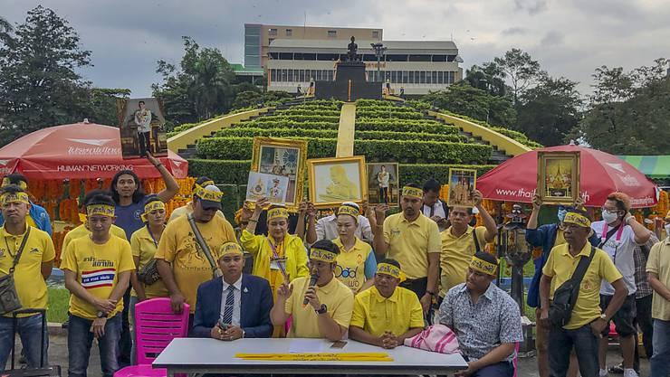 Demonstranten tragen gelbe Kleidung und halten Abbildungen des thailändischen Königs Maha und der Königin Suthida bei einem Protest vor der Ramkhamhaeng Universität, um ihre Loyalität für die Institution unter Beweis zu stellen. Foto: Peerayot Lakkananukul/AP/dpa
