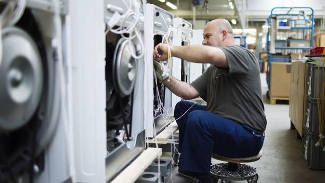 Ein Angestellter der Firma Schulthess montiert Waschmaschinen (Archiv)