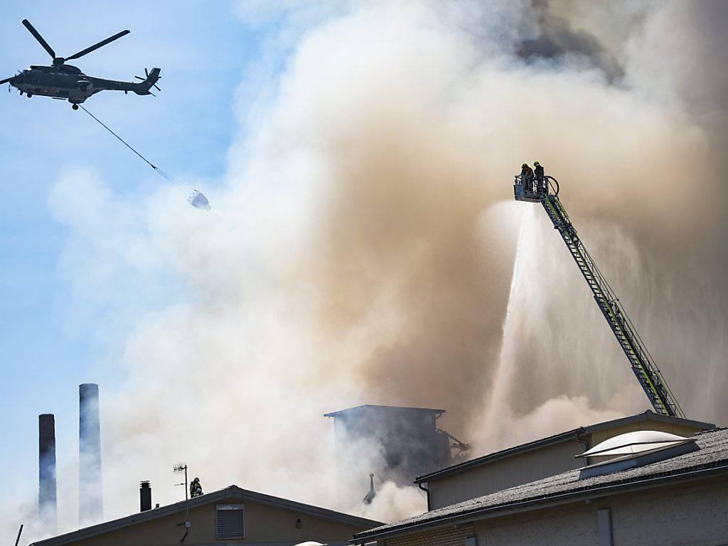 Löscharbeiten auf dem Raduner-Areal in Horn TG am Montag. Auch am Dienstag musste die Feuerwehr noch den ganzen Tag immer wieder Glutnester löschen. (Bild: KEYSTONE/Gian Ehrenzeller)