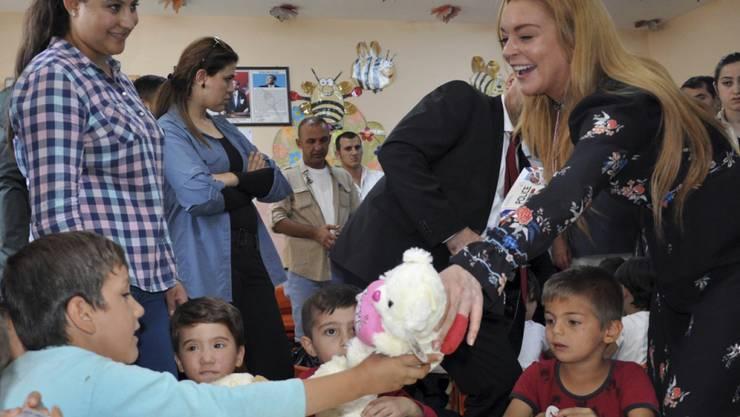 Die einstige Skandalnudel Lindsay Lohan letzten Oktober beim Geschenkeverteilen in einem syrischen Flüchtlingslager in Istanbul. Nachdem sie sich jüngst mit dem Islam zu beschäftigen begann heisst es, sie wolle konvertieren. (Archivbild)