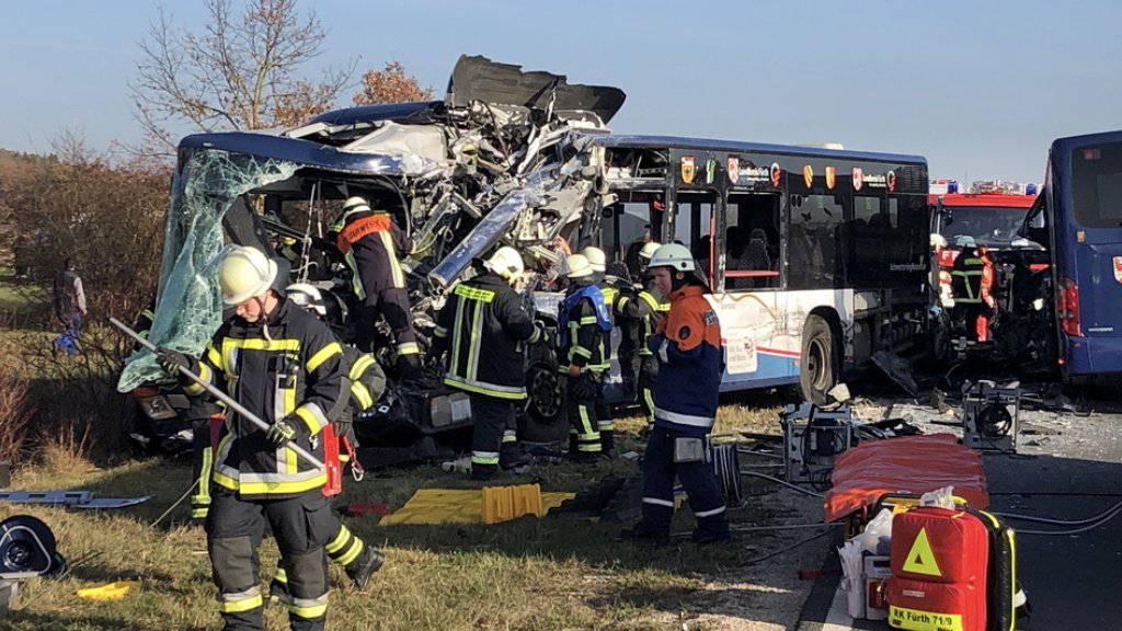 Rettungskräfte arbeiten an der Unfallstelle. Bei dem Zusammenstoss von zwei Schulbussen im Landkreis Fürth sind mehrere Kinder schwer verletzt worden.