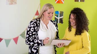 Sie leiten die «KiTa nano» in Baar: Stefanie Grunder (links) und Vanessa Perroncello setzen auf Digitalisierung. Via App auf dem Tablet werden die Informationen über ihre Schützlinge erfasst.