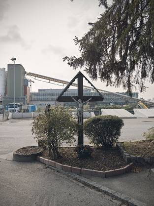 Ein Kruzifix steht am Grenzübergang zwischen der Schweiz und Frankreich. Das Kieswerk, das auf Schweizer Seite steht, wird von französischer Seite mit den Lastwagen angefahren. Dahinter wächst die Silicon Mile.
