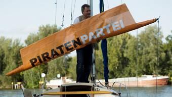 Die deutsche Piratenpartei in Schieflage: Ein Mitglied der Piratenpartei rollt in Berlin am Spreeufer ein Segel ein.