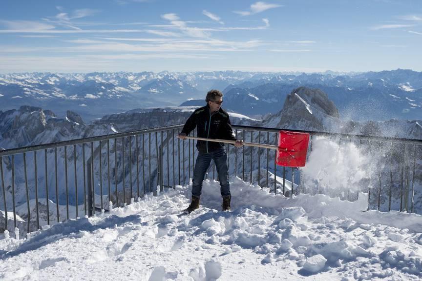 Gust Broger schaufelt Schnee auf dem Gipfel, am Freitag, 24. Oktober 2014, auf dem Saentis (2501,9 Meter). (KEYSTONE/Gian Ehrenzeller)