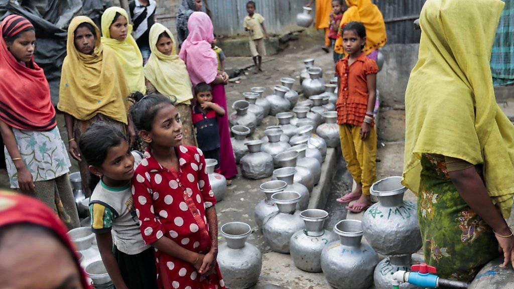 Nach Bangladesch geflohene Rohingya-Frauen und Kinder stehen an für Wasser