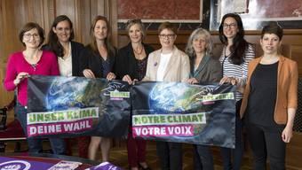 Acht von zwölf Ständeratskandidatinnen der Grünen posieren erst mit der Klima-, dann mit der Frauenstreik-Fahne (auf dem Tisch) vor der Kamera.