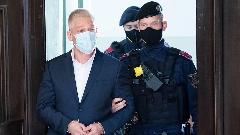 Beamte begleiten Julian Hessenthaler (l), Privatdetektiv aus Österreich, in den Gerichtssaal. Der mutmaßliche Drahtzieher in der Ibiza-Affäre ist außerdem wegen Drogenhandels angeklagt. Foto: Roland Schlager/APA/dpa