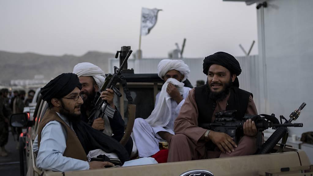 Taliban-Kämpfer sitzen auf der Ladefläche eines Autos auf dem Gelände des Flughafens in Kabul und halten Waffen in ihren Händen.