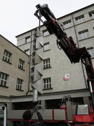 Mit einem Kran wird die neue Installation auf das Dach des Dietiker Zentralschulhauses gehievt