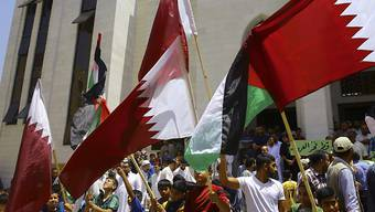 Solidaritäts-Kundgebung für Katar im Gazastreifen. Demonstranten mit der weinrot-weissen Katar-Flagge sowie der palästinensischen Flagge