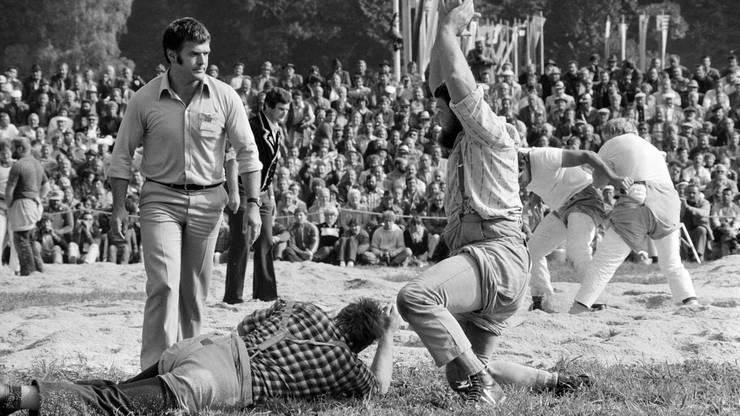 Joerg Schneider, rechts, jubelt nach seinem Sieg gegen Leo Betschart, links, bei einem Gang beim Unspunnen-Schwinget, aufgenommen am 6. September 1981 bei Interlaken. Betschart profitiert spaeter vom gestellten Schlussgang zwischen Joerg Schneider und und Heinz Seiler und wird mit knappem Vorsprung Sieger des Unspunnen-Schwingets.