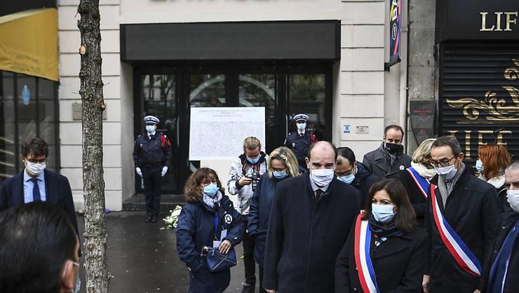 Der französische Premierminister Jean Castex (4.v.r) und die Pariser Bürgermeisterin Anne Hidalgo (3.v.r) nehmen an einer Kranzniederlegungszeremonie anlässlich des 5. Jahrestages der Anschläge vom 13. November 2015 vor der Konzerthalle Bataclan teil. Foto: Christophe Archambault/AFP POOL/AP/dpa