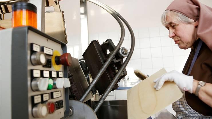Produktion in vier Schritten: Schwester Therese bedient den Backautomaten,