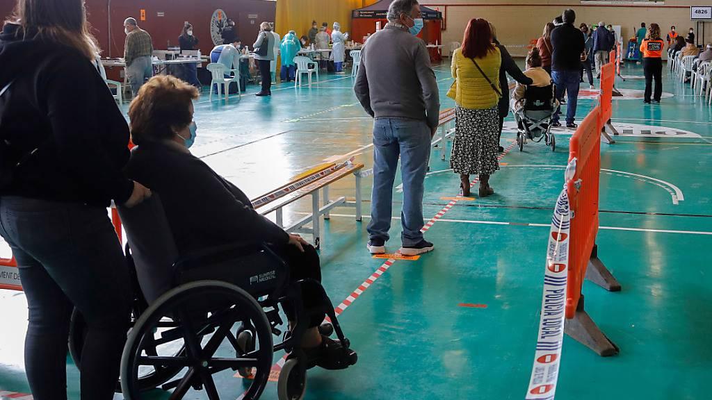 Menschen warten in einer Sporthalle in Lloseta, Mallorca, darauf, auf Covid-19 getestet zu werden. Foto: Clara Margais/dpa