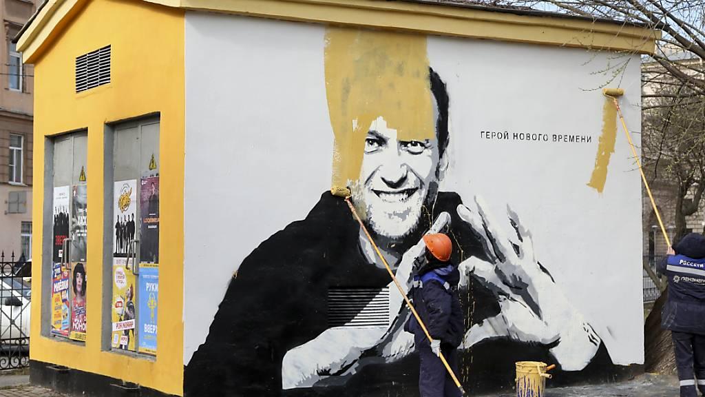 Ein Graffiti mit dem Konterfei des inhaftierten russischen Oppositionsführers Nawalny in St. Petersburg wird übermalt. Auf der Wand ist zu lesen: «Held unserer Zeit». Foto: Valentin Egorshin/AP/dpa