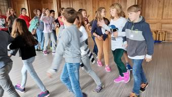 Die zehn- und elfjährigen Fünftklässler üben im Singsaal des Stapferschulhauses für den grossen Auftritt im Dezember. Auch die Lehrpersonen tanzen in der Gruppe mit.