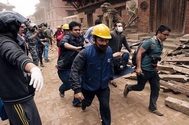 Helfer bergen Überlebende aus den Trümmern in Kathmandu.