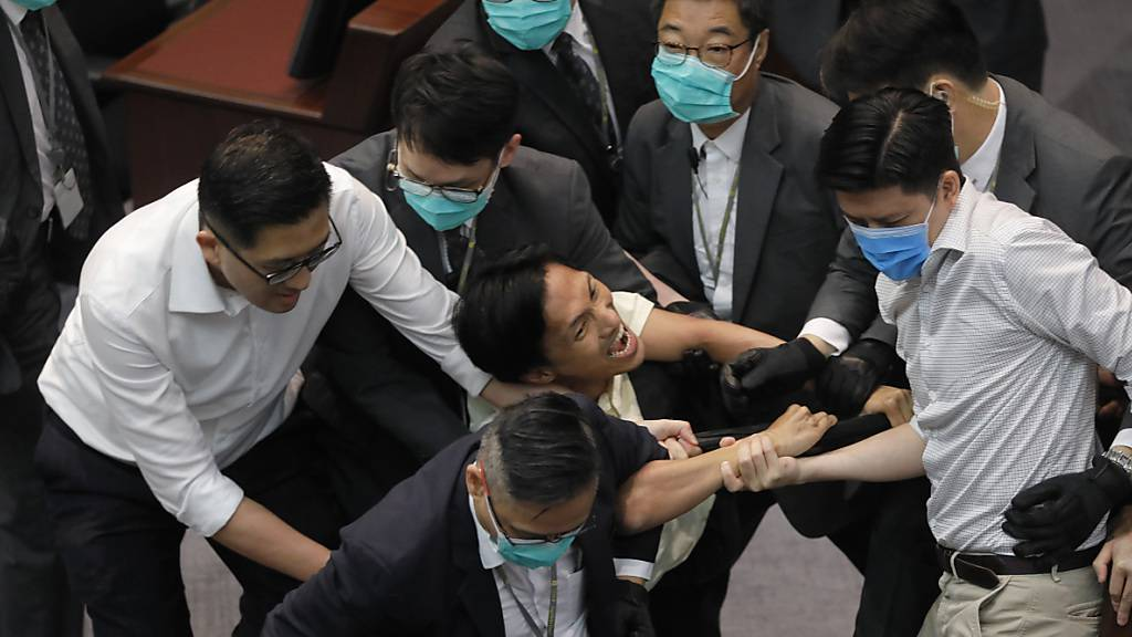 Eddie Chu Hoi-Dick (M), Mitglied des Legislativrates, wird von Sicherheitskräften abgeführt, nachdem es während einer Ausschusssitzung des Legislativrats zu Auseinandersetzungen zwischen den Teilnehmern kam. Foto: Vincent Yu/AP/dpa