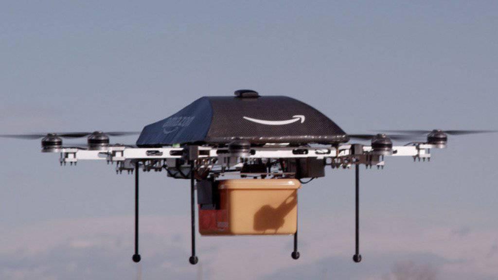 An eine Mini-Drohne des Online-Händlers Amazon ist eine Paketkiste befestigt. In 30 Minuten soll die Fracht beim Kunden eintreffen. (Archiv)