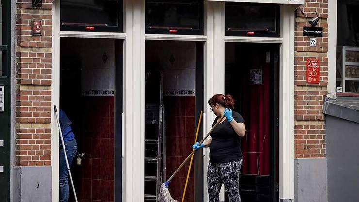 """Eine Frau reinigt im Rotlichtviertel Wallen den Zugang zu Räumlichkeiten, die The Office 52 an Sexarbeiter vermietet. Ab 01.07.2020 dürfen nach einem Beschluss der Regierung alle Sexarbeiter im Land wieder uneingeschränkt ihrem Gewerbe nachgehen. Foto: """"robin Van Lonkhuijsen""""/ANP/dpa"""