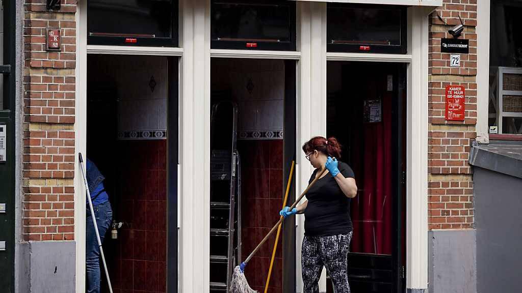 Eine Frau reinigt im Rotlichtviertel Wallen den Zugang zu Räumlichkeiten, die The Office 52 an Sexarbeiter vermietet. Ab 01.07.2020 dürfen nach einem Beschluss der Regierung alle Sexarbeiter im Land wieder uneingeschränkt ihrem Gewerbe nachgehen. Foto: «robin Van Lonkhuijsen»/ANP/dpa