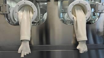 Manche Handschuhe in den Laboratorien bleiben leer, weil die dazugehörigen Spezialisten fehlen.