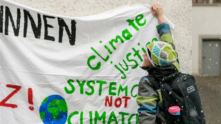 Ein Schüler hängt im Vorfeld des Streiks das Transparent für den Klimastreik auf.