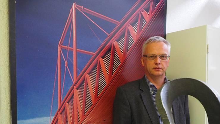 Markus Amsler vor einem Bild der Autobahntankstelle in Piotta – entworfen von Mario Botta, gebaut von der Jakem AG. twe