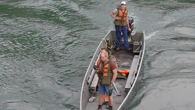 Helfer suchen mit einem Boot nach den vermissten Personen am Rhein in Bad Säckingen.