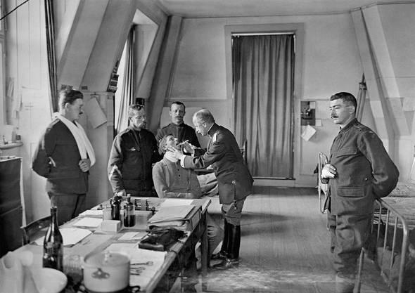 Ein Schweizer Truppenarzt untersucht während des Ersten Weltkrieges Soldaten in einem Krankenzimmer.
