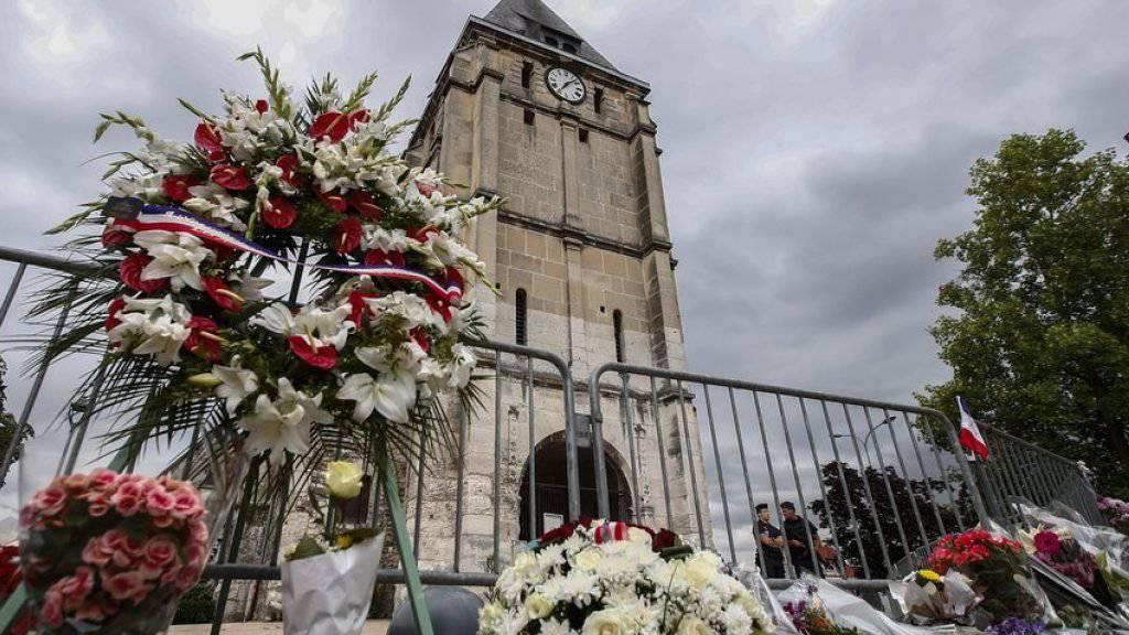 Blumen bei der Saint-Etienne-Kirche nahe Rouen, wo zwei Angreifer einen Priester ermordeten. Nun ist auch der zweite der beiden Täter offiziell identifiziert worden.