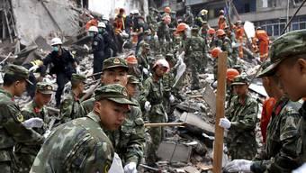 Rettungshelfer suchen in den Trümmern von eingestürzten Häusern in Ostchina nach Überlebenden.